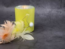 Burning candle with rabbit covered with colorful feathers on concrete background. Burning candle covered with colorful feathers on concrete background royalty free stock photography