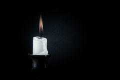 Burning candle on a dark background Stock Photo