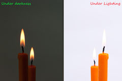 Burning candle between dark and bright Stock Photos