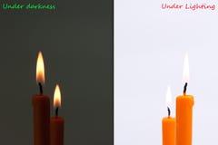 Burning candle between dark and bright Stock Photos
