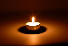 Burning candle in darkness. Small flame of a burning candle in darkness Stock Photography