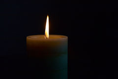 Burning candle in the darkness Royalty Free Stock Photos