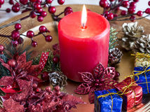 Burning candle on decorated Christmas plate Stock Photos