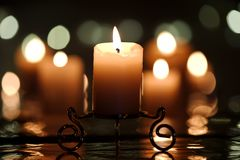 Burning candle on a decorative stand Stock Photo