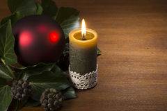 Burning candle with evergreen branch and red xmas ball. On wooden Stock Photo