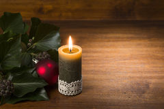 Burning candle with evergreen branch and red xmas ball. On wooden Stock Image