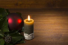 Burning candle with evergreen branch and red xmas ball on wooden Stock Images