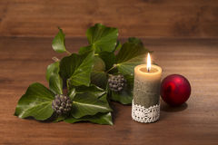 Burning candle with evergreen branch and red xmas ball on wooden. Old styled xmas still life Stock Images