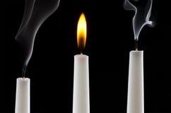 Burning candle with extinguished candles stock image