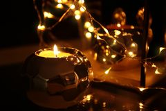 Burning candle and fairy lights as decor, Royalty Free Stock Photos