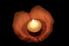 Burning candle in female hands Royalty Free Stock Photos