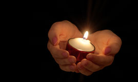 Burning candle in female hands Royalty Free Stock Image