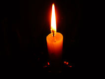 Burning candle flame. Wax candle burning with a beautiful flame on a black background stock image