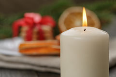 Burning candle in front of christmas table Royalty Free Stock Photos
