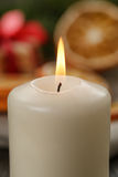 Burning candle in front of christmas table Stock Image
