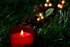 Burning candle in front of cones with green fir Royalty Free Stock Photography