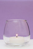 Burning candle front view,  on purple Royalty Free Stock Photography