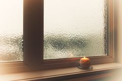 Burning candle and frosted window in hazy light. Winter composition Royalty Free Stock Photos