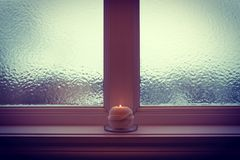 Burning candle and frosted window in winter twilight. Burning candle and frosted window in twilight. Cozy winter evening Stock Image
