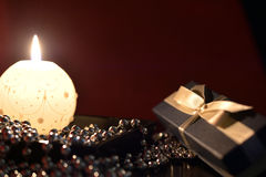 Burning candle, gift box and Christmas decorations Royalty Free Stock Image