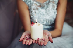 A burning candle in the girl`s hands. Girl holding a burning candle on the palms Royalty Free Stock Photo
