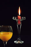 The burning candle. And a glass of juice isolated on black background Stock Photography