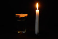 Burning candle, a glass with water and breads. Composition from a burning candle, a glass with water and breads Royalty Free Stock Photography