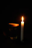 Burning candle, a glass with water and breads. Composition from a burning candle, a glass with water and breads Royalty Free Stock Photos