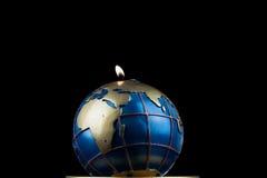 Burning candle globe on black Royalty Free Stock Photo