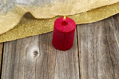 Burning candle with gold colored ribbon on rustic wooden boards Stock Photography