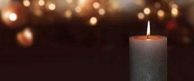 Burning candle with golden bokeh Stock Images