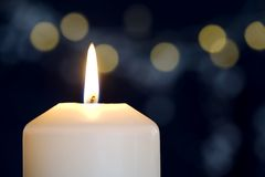Burning candle with golden lights Royalty Free Stock Photo