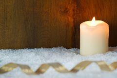 Burning candle with golden ribbon. In snow Stock Photos