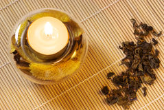 Burning candle and green tea. Burning scented candle witn dried flowers and green tea on wood mat Stock Photos