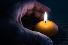 Burning candle with hand in the dark Royalty Free Stock Photo