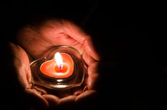 Burning candle in hands. Burning candle with heart shape in hands Stock Photography