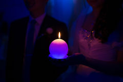 Burning candle in hands of the newlyweds Stock Photos