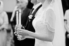 Burning candle at hands of wedding couple in church.  Stock Image