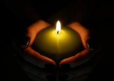 Burning candle in the hands Royalty Free Stock Photography