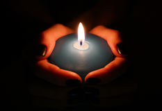 Burning candle in the hands Stock Images