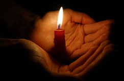 Burning candle in the hands Royalty Free Stock Image