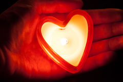 Burning candle heart on hand Stock Photos