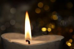 Burning candle in heart shape with christmas lights Stock Photography