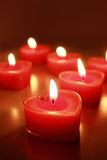 Burning candle hearts. Burning red candle hearts on the table Royalty Free Stock Image