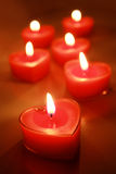 Burning candle hearts. Burning red candle hearts on the table Royalty Free Stock Images