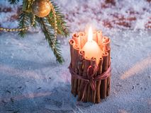 Burning candle in a candlestick against a snowy background. Royalty Free Stock Photo