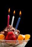 Burning candle on ice cream Stock Photos