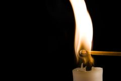 Burning Candle with Match. A match being ingited by a burning candle Royalty Free Stock Image