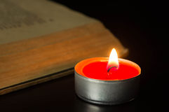 The burning candle near the open book Royalty Free Stock Photo