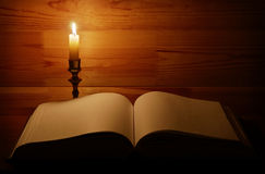 Burning candle near open old book Stock Image